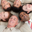 Business team lying on the floor with heads together — Stockfoto