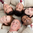 Foto Stock: Multi-ethnic business team lying in circle