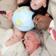Multi-ethnic business team lying on the floor around a terrestri — Stock Photo