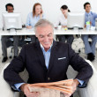 Smiling businessman reading a newspaper - Stock Photo