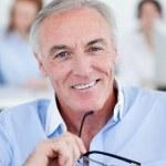 Senior businessman holding glasses — Stock Photo #10280902