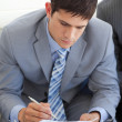Concentrated businessman writing while waiting for a job intervi - Stock Photo