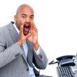 Afro-american businessman yelling sitting at his desk - Stock Photo