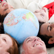 Multi-ethnic business lying around a globe — Stock Photo #10281496