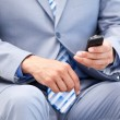 Close-up of a businessman sitting on a wheelchair sending a text — Stock Photo