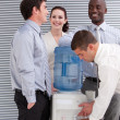 Stock Photo: Smiling multi-ethnic business interacting at a watercoole