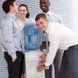 Stock Photo: Confident multi-ethnic business interacting at a watercoo