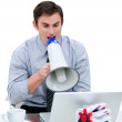 Angry businessman yelling through a megaphone sitting at his des - Stock Photo