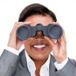 Assertive businesswoman looking through binoculars — Stock Photo #10282107