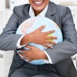 Close-up of a smiling businesswoman holding a terrestrial globe — Stock Photo
