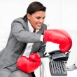 Young businesswoman wearing boxing gloves punching a computer — Stock Photo