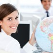 Smilling businesswoman holding a globe — Stock Photo