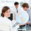 Confident businesswoman holding a globe — Stock Photo #10282259