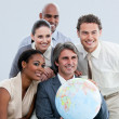 Multi-ethnic businessteam holding a globe in the office — Stock Photo