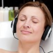 Close-up of a relaxed young woman listening music in a bubble ba — Stock Photo #10282398
