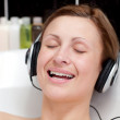 Smiling young woman listening music in a bubble bath — Stock Photo #10282402