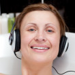 Cheerful woman using headphones in a bubble bath — Stock Photo #10282406
