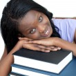 Smiling student leaning on a stack of books — Stock Photo
