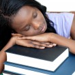 Exhausted student leaning on a stack of books — Stockfoto