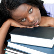 Tired student leaning on a stack of books — Stock Photo