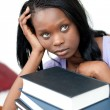 Upset student leaning on a stack of books — ストック写真