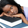 Stock Photo: Annoyed student leaning on stack of books