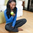 Stock Photo: Happy woman eating an apple sitting on the floor