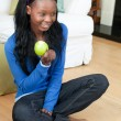 Jolly woman eating an apple sitting on the floor - Stock Photo