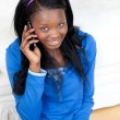 Smiling woman talking on phone in the living-room — Stockfoto