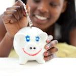 ragazza adolescente afro-americana, mettendo i soldi in un salvadanaio — Foto Stock