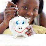 ragazza adolescente allegra mettendo soldi in un salvadanaio — Foto Stock