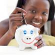 sorridente ragazza adolescente mettendo soldi in un salvadanaio — Foto Stock