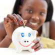 Happy teen girl putting money in a piggy-bank — Stockfoto