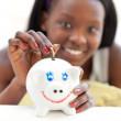 ragazza adolescente felice mettendo soldi in un salvadanaio — Foto Stock