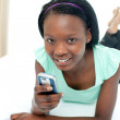 Pretty teen girl using a mobile phone lying on her bed — Stock Photo
