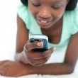 Afro-American teen girl using a mobile phone lying on her bed — Stock Photo