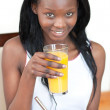 Smiling Afro-American drinking an orange juice — Stock Photo