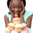 Surprised young woman looking at cakes — Stock Photo #10283125