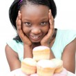 Cheerful young woman looking at cakes — Stock Photo #10283130