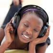 Royalty-Free Stock Photo: Cute woman listening music with headphones lying on a sofa