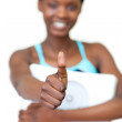 Cheerful fitness woman with thumb up holding a weight scale — Stock Photo