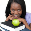 Young student holding books smiling at the camera — Stock Photo