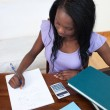 Concentrated Afro-American teen girl doing her homework — Stock Photo