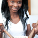 mujer afro-americana sonriente preparar una ensalada — Foto de Stock   #10283398