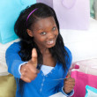 Smiling teen girl with thumb up shopping on-line — Stock Photo