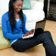 Afro-american woman using a laptop sitting on the floor — Foto Stock