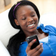 Happy woman sending a text lying on a sofa — Stock Photo