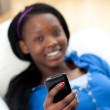Afro-American woman sending a text lying on a sofa — Stock Photo #10283469
