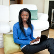 Young woman using a laptop sitting on the floor — Stock Photo