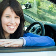 Happy teen girl smiling at the camera sitting in her car — Stock Photo #10283753